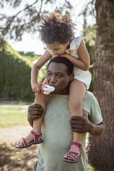 Happy family. dark-skinned cute kid sitting on her dads shoulders