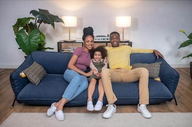 행복한 가족. 어두운 피부의 귀여운 소녀와 젊고 아름다운 부모가 조명이 켜진 방에서 소파에 함께 앉아 있습니다.