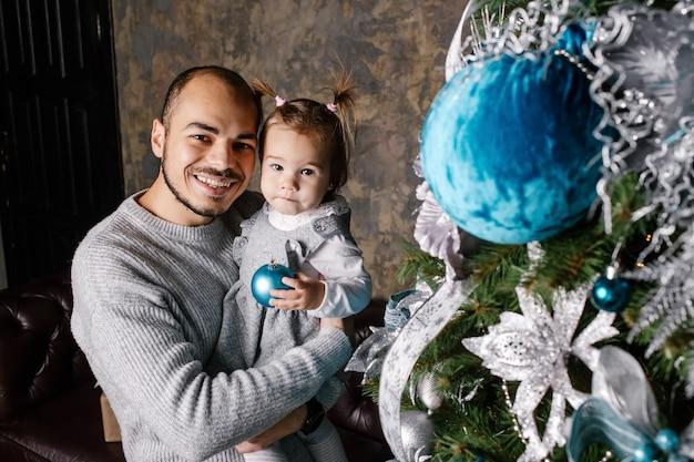 幸せな家族は家でクリスマスツリーを飾ります。