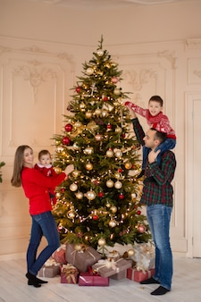 Happy family decorate the christmas tree indoors together. loving family. merry christmas and happy holidays.