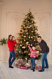 Happy family decorate the christmas tree indoors together. loving family. merry christmas and happy holidays