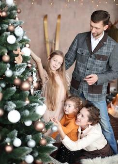 행복한 가족은 거실에 크리스마스 트리를 장식합니다.