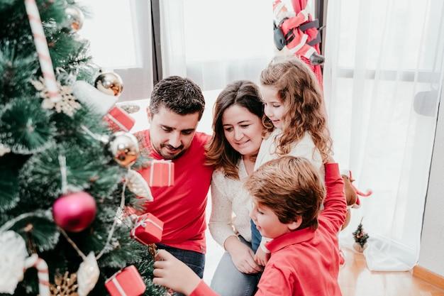 家でクリスマスツリーを飾る幸せな家族