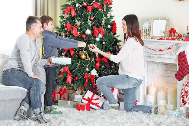 休日のリビングルームでクリスマスツリーを飾る幸せな家族