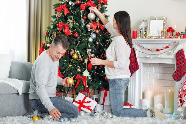 Счастливая семья украшает елку в праздничной гостиной
