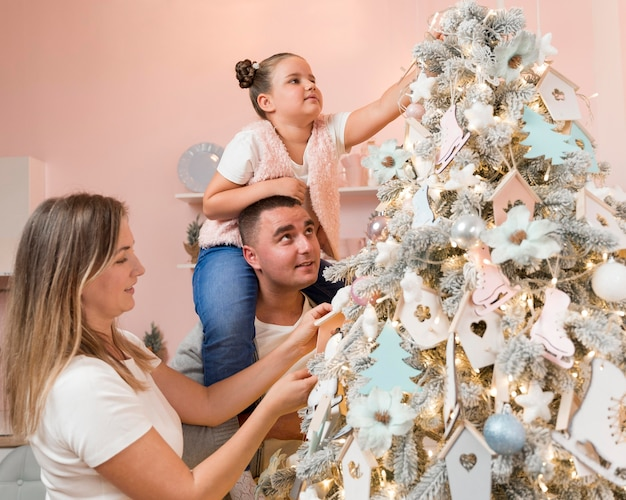 Happy family decorating the christmas tree