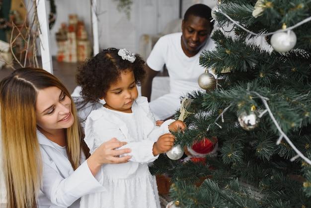 クリスマスツリーを飾る幸せな家族
