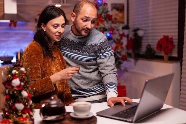 クレジットカードを使用してクリスマスプレゼントを購入するオンラインショッピングをしている幸せな家族