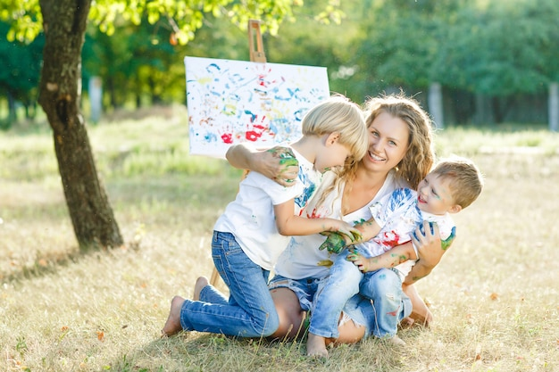 Happy family drawing outdoors. young mother having fun with her little children