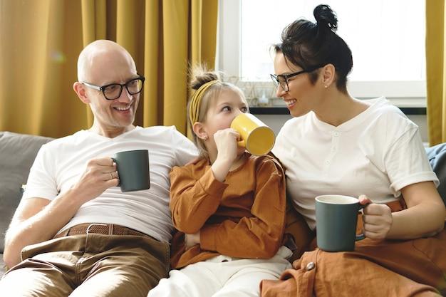 Счастливая семья пьет горячий чай в гостиной своей уютной квартиры