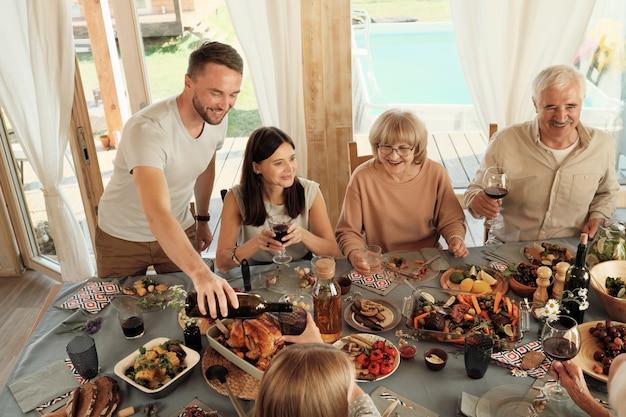 Счастливая семья пьет вино и ест вкусные блюда, сидя за столом, вместе празднуя праздник