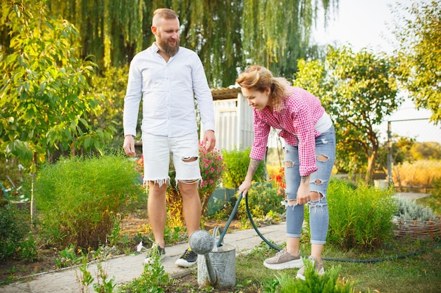 Happy family during watering plants in a garden