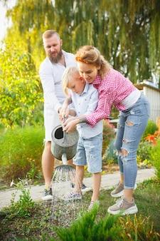 야외 정원에서 식물에 물을 주는 동안 행복한 가족