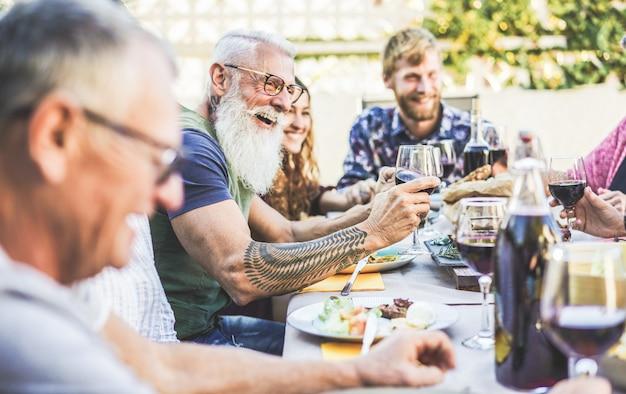 屋外のパティオでバーベキューディナーでワインを食べたり飲んだりして幸せな家族