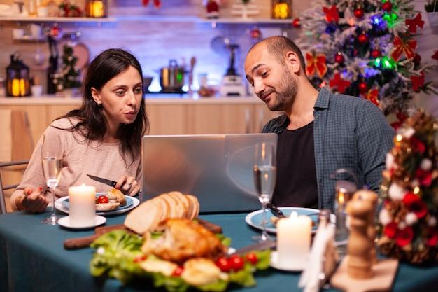 ダイニングテーブルに座っておいしいクリスマスディナーを食べる幸せな家族