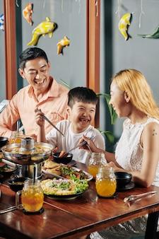 レストランで夕食を食べて幸せな家族