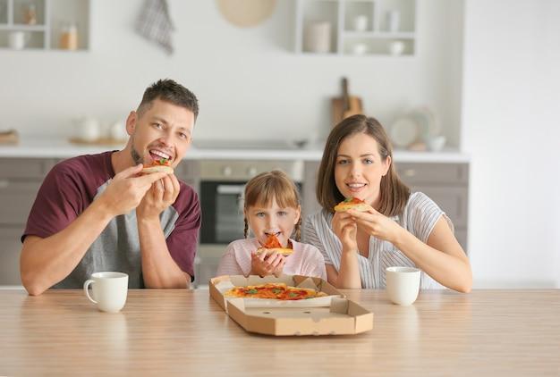 집에서 피자를 먹는 행복 한 가족