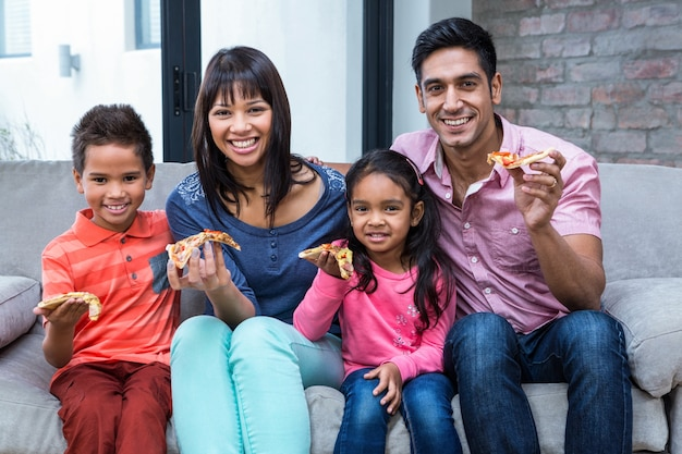 Счастливая семья, едят пиццу на диване