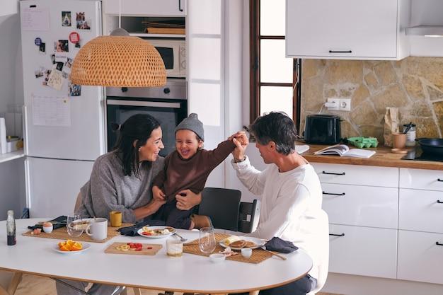 식탁에서 솔직한 딸을 껴안은 행복한 가족