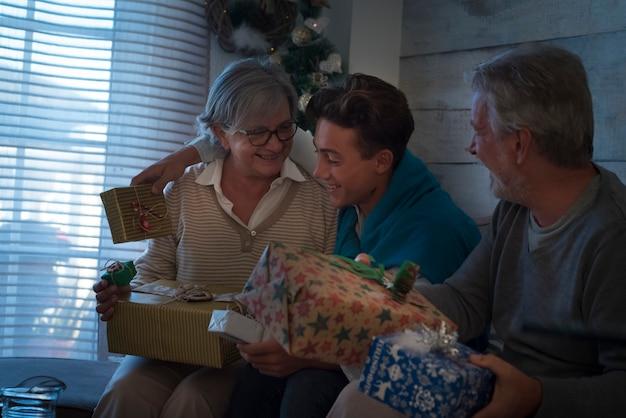 幸せな家族は贈り物と一緒に家でクリスマスイブの夜をお楽しみください