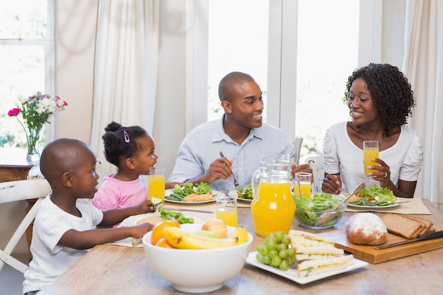 Счастливая семья, наслаждаясь здоровой едой вместе