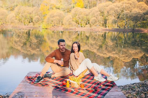 ピクニックで湖で秋の日を楽しんで幸せな家族