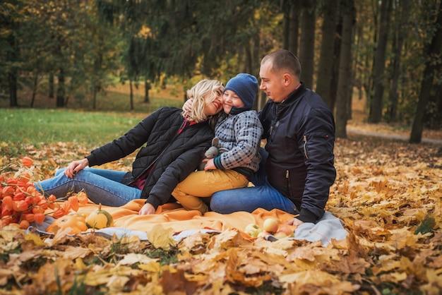 Happy family enjoying autumn picnic. mom dad and son.