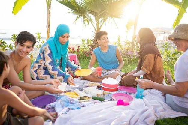 Happy family enjoying picnic on beach near sea
