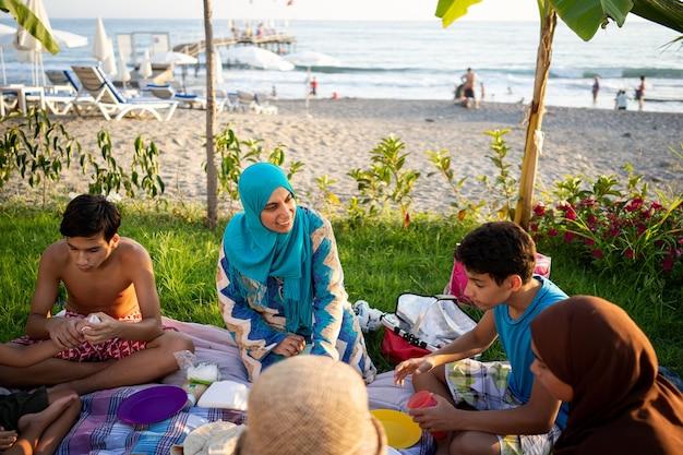 海の近くのビーチでピクニックを楽しんで幸せな家族