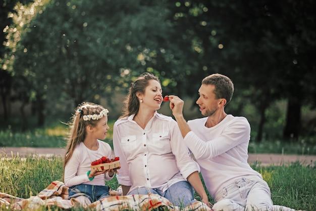 피크닉에서 딸기를 즐기는 행복 한 가족