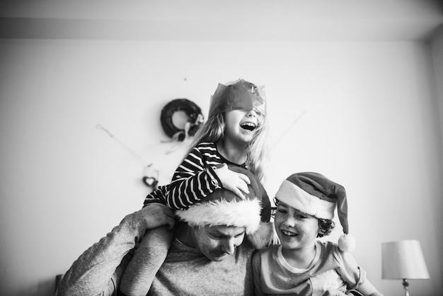 Счастливая семья, наслаждаясь рождественским праздником дома