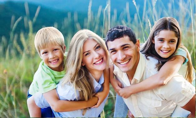 背景にぼやけたフィールドで休暇otdoorsを楽しんで幸せな家族
