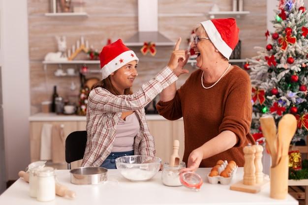 おばあちゃんの鼻に小麦粉を入れて冬の季節を楽しんで幸せな家族