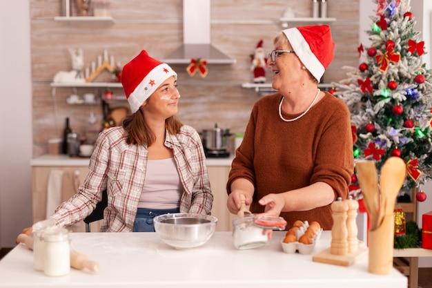 一緒に自家製の伝統的なクッキーを準備して冬の季節を楽しんでいる幸せな家族