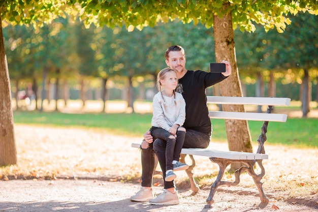 Happy family in fall. father and little kid have fun taking selfie on beautiful autumn day