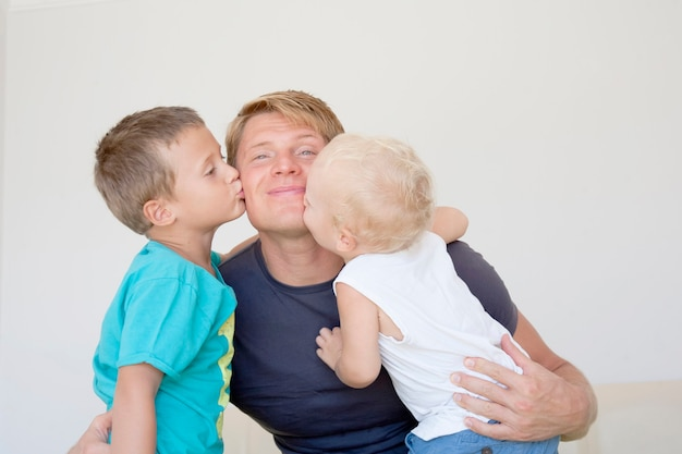幸せな家族。家で父と2人の息子の家族の幸せな肖像画