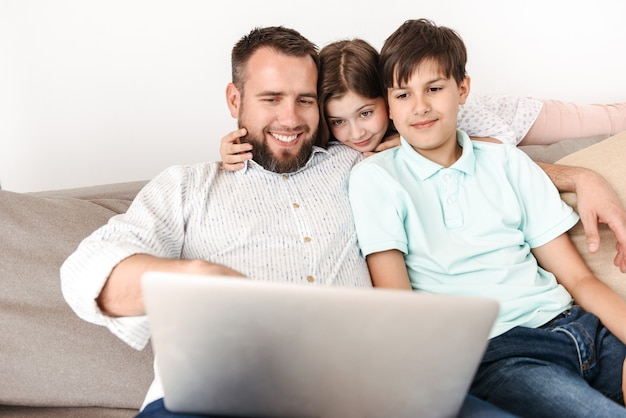 Счастливый семейный отец 30 лет с сыном и дочерью сидят вместе на диване у себя дома и используют серебристый ноутбук