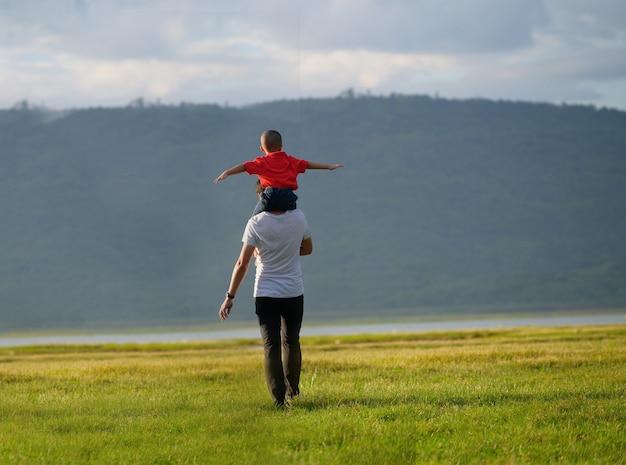 幸せな家族の父と子の牧草地で実行されています