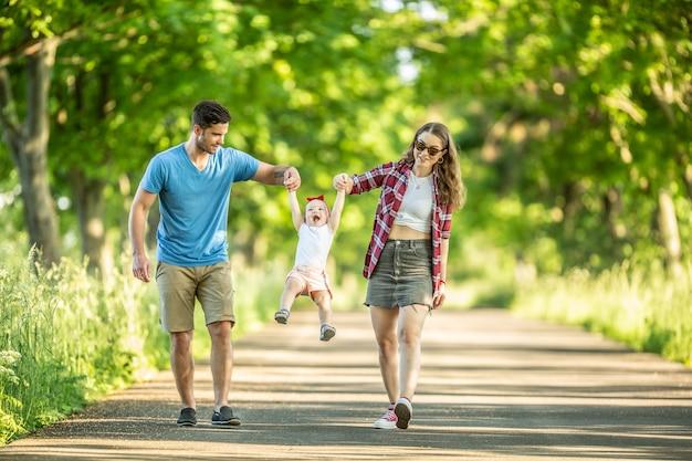 幸せな家族、父と母は彼らの小さな娘と一緒に公園で散歩を楽しんでいます。