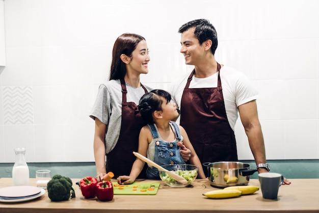 幸せな家族の父と娘のキッチンで一緒に料理と食事の準備を持つ母