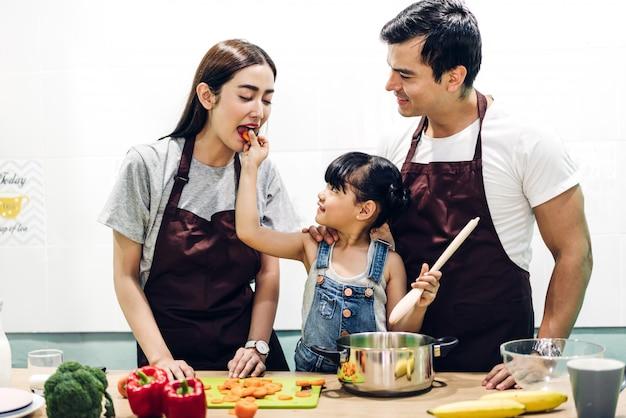 Счастливая семья, отец и мать с дочерью, приготовление пищи на кухне