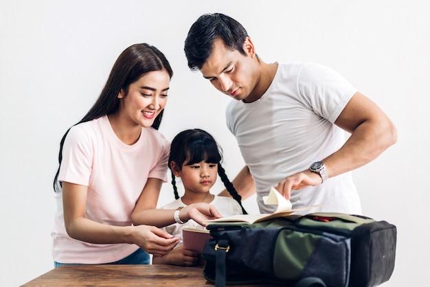 Счастливая семья, отец и мать с дочерью упаковывают школьную сумку с книгами, прежде чем идти в школу дома