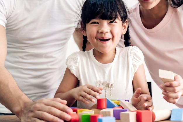 작은 귀여운 소녀와 함께 행복 한 가족 아버지와 어머니는 집에서 테이블에 나무 블록 장난감을 재생하는 동안 즐길 수
