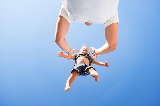 Счастливая семья, отец и сын. папа бросает ребенка высоко над собой