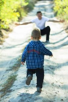 Счастливая семья. отец и сын, играя и обнимая на открытом воздухе. день отца