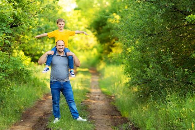 Счастливая семья: отец и сын гуляют в природе летом. сын сидит на спине отца.