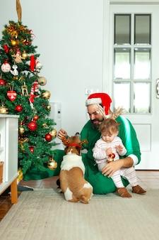 Счастливая семья отец ребенок дочь и собака украшают елку
