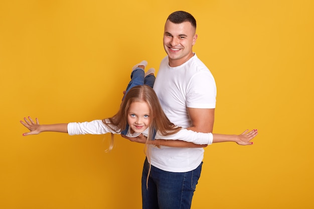Happy family father and daughter, child desses denim onalls pretending being plane with their hands spreading aside and having fun with her daddy, isolated on yellow wall