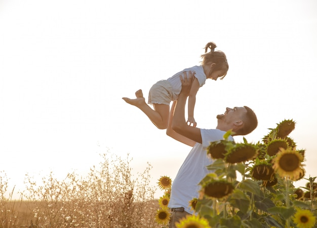 Happy family, father and daughter playing in the field