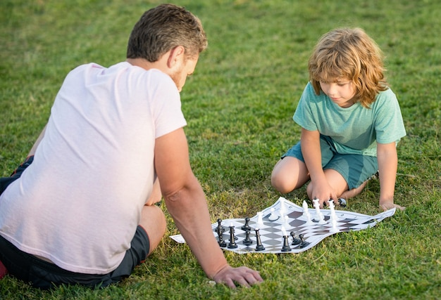 Happy family of father man and son boy playing chess on green grass in park outdoor, opponent.